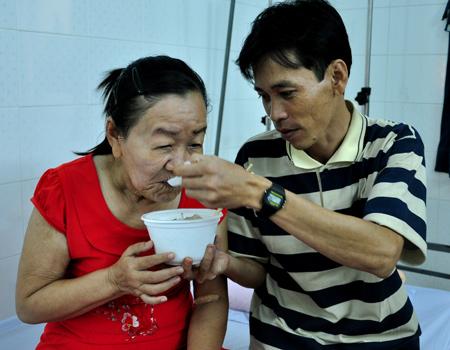 Anh Nguyễn Thành Tuyển, chồng Phượng, ân cần yêu thương chăm sóc vợ tại bệnh viện ở TP HCM, như ngày cô còn xinh đẹp. Ảnh: Thiên Chương