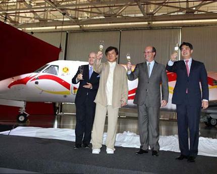 Thành Long (thứ hai từ trái sang) có mặt tại Brazil nhận chiếc phi cơ riêng trị giá 30 triệu USD của anh.