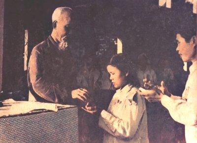 """Bác Hồ gắn huy hiệu cho anh hùng thủy lợi Phạm Thị Vách tại xã Hùng Cường, Kim Động, Hưng Yên năm 1960. Chị Phạm Thị Vách nổi tiếng trong các phong trào thủy lợi """"vắt đất ra nước, thay trời làm mưa"""", """"nghiêng đồng đổ nước ra sông"""". Tuổi đôi mươi, chị Vách là kiện tướng thủy lợi. 22 tuổi được phong Anh hùng lao động và hai năm sau, trở thành đại biểu Quốc hội liên tiếp ba khóa III, IV, V. Tự hào hơn, """"nữ Sơn Tinh"""" Phạm Thị Vách đã vinh dự hai lần được nhận Huy hiệu Bác Hồ."""