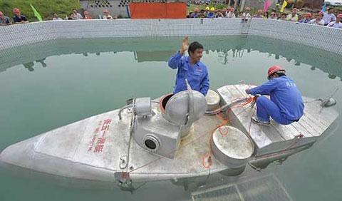Zhang Wuyi vẫy tay chào mọi người trước khi đưa tàu ngầm tự chế lặn xuống nước ở Vũ Hán, tỉnh Hồ Bắc, hôm qua. Ảnh: China Daily