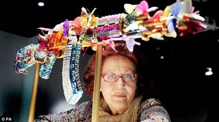 Nghệ sĩ Laila Shawa tạo dáng cùng tác phẩm của mình - một khẩu súng AK47 gắn bươm bướm đủ màu sắc.