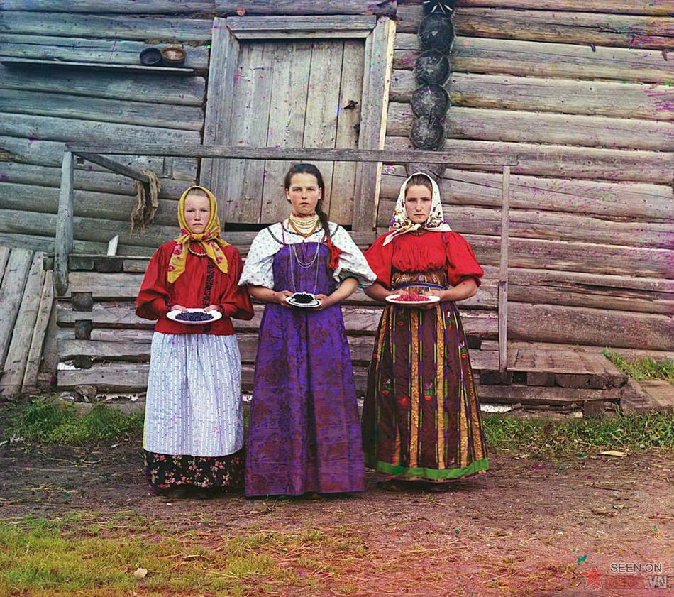 Các cô thôn nữ đứng bên ngôi nhà gỗ truyền thống, trên tay là những đĩa hoa quả phục vụ khách. Ảnh chụp ở một khu vực nông thôn dọc theo sông Sheksna, gần thị trấn Kirillov, 1909.