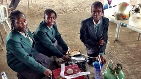Ba trong số bốn nữ sinh bên cạnh chiếc máy phát điện chạy bằng nước tiểu
