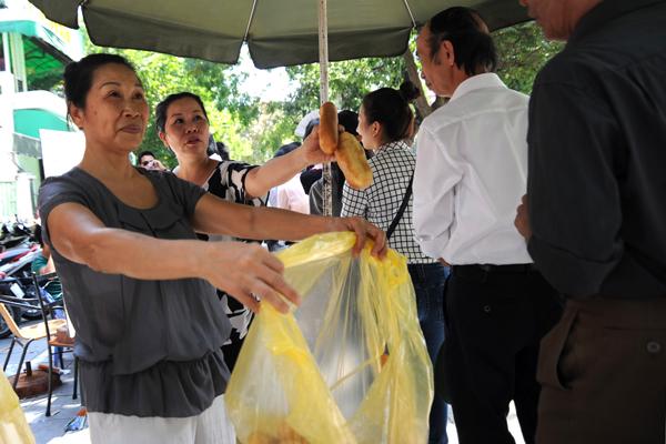 Cô Thu, chủ quán cà phê trên đường Điện Biên Phủ, đang cùng người nhà phát bánh mỳ miễn phí cho người dân đang xếp hàng vào viếng Đại tướng