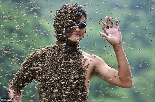 Lv vẫy tay chào mọi người khi ong đang bâu đầy trên cơ thể.
