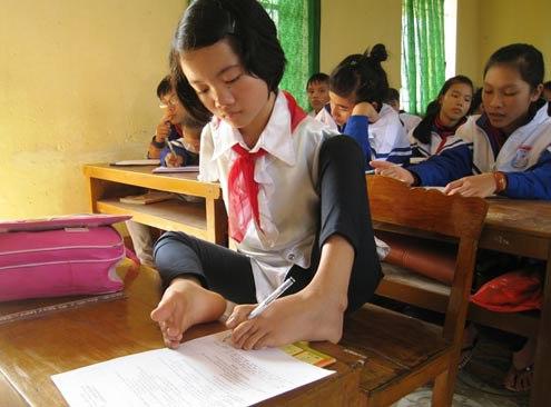 Để việc học chữ của con gái được thuận tiện, người cha đã sáng chế ra một chiếc bàn phù hợp với thân hình nhỏ bé của em. Ảnh: Lê Hoàng.