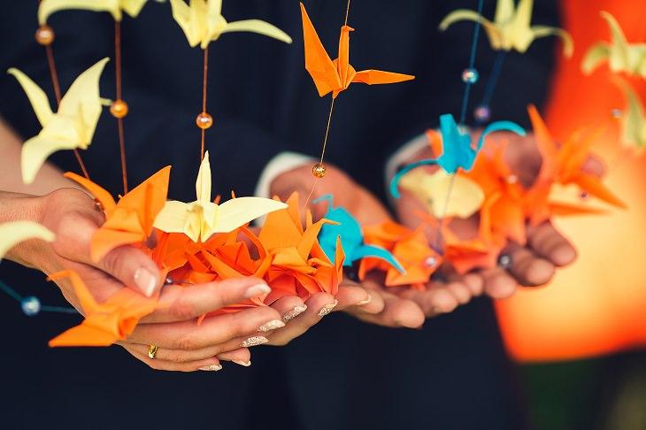 Origami từ giấy màu để trang trí đám cưới, với hình dáng những con hạc treo trên dây.