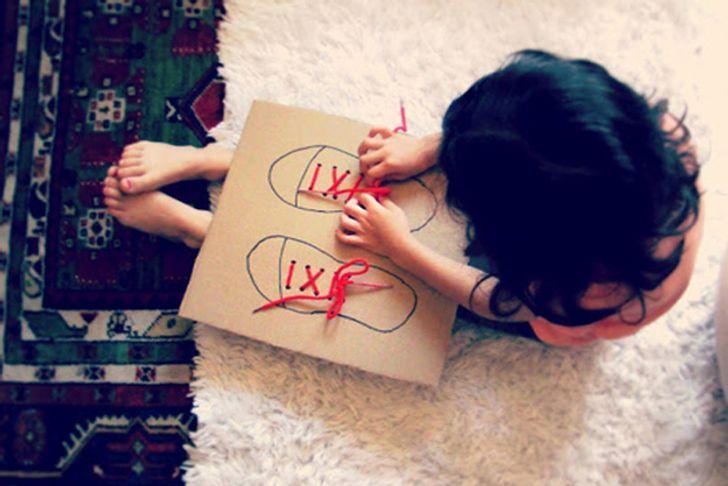 Cho trẻ tập thắt dây giày với một mảnh bìa cứng và hai sợi dây
