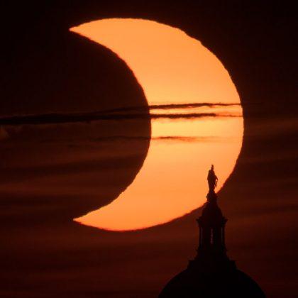 Nhật thực một phần được nhìn thấy khi mặt trời mọc phía sau Tượng Tự do trên đỉnh Tòa nhà Quốc hội Hoa Kỳ vào ngày 10 tháng 6 năm 2021, được chụp từ Arlington, Virginia bởi nhiếp ảnh gia Bill Ingalls của NASA.