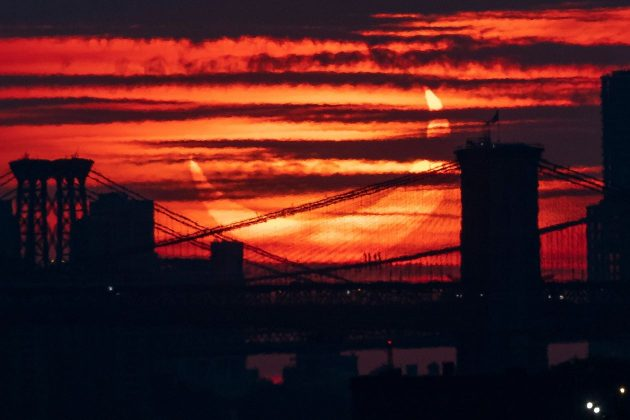 Nhật thực mọc lên trên những cây cầu bắc qua sông Đông ở New York.
