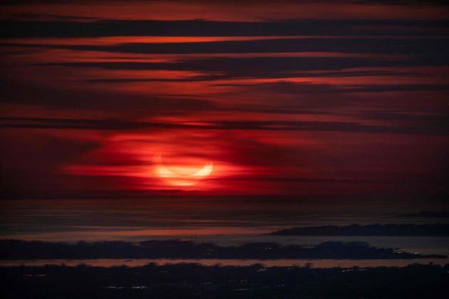 Mặt trời mọc bị che khuất một phần từ phía sau cửa sổ một tòa nhà cao tầng ở Thành phố New York.
