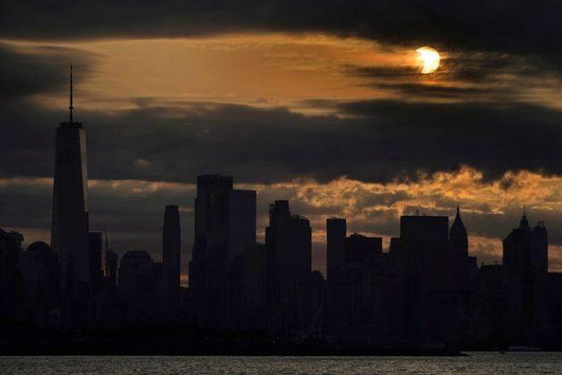 Mặt trời bị che khuất một phần khi nó mọc ở phía dưới Manhattan ở New York, Thứ Năm, ngày 10 tháng 6 năm 2021