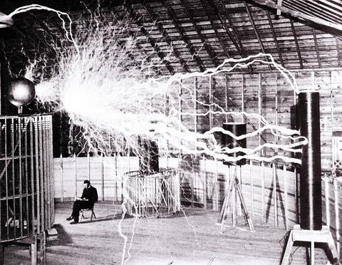"""Bức ảnh công khai của Nikola Tesla trong phòng thí nghiệm của ông ở Colorado Springs, Colorado, vào tháng 12 năm 1899. Tesla chụp ảnh với """"máy phát phóng đại"""" của mình, có khả năng tạo ra hàng triệu vôn điện. Chiều dài phóng điện được hiển thị là 6,7 mét (22 feet)."""