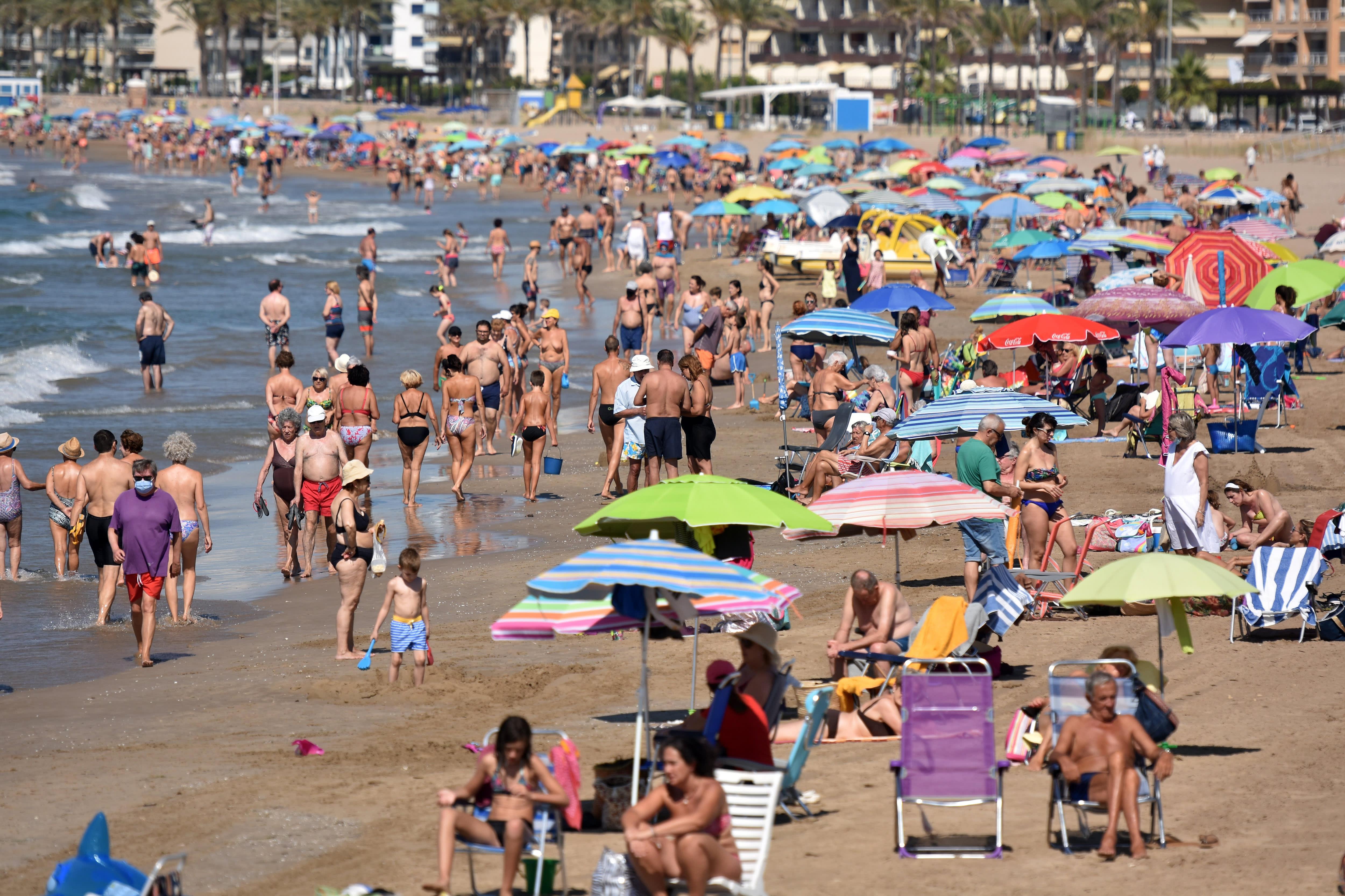 Mọi người tận hưởng ánh nắng mặt trời và thời tiết ấm áp tại Bãi biển Segur de Calafell ở Tây Ban Nha, nơi các ca bệnh beta đang tăng lên.