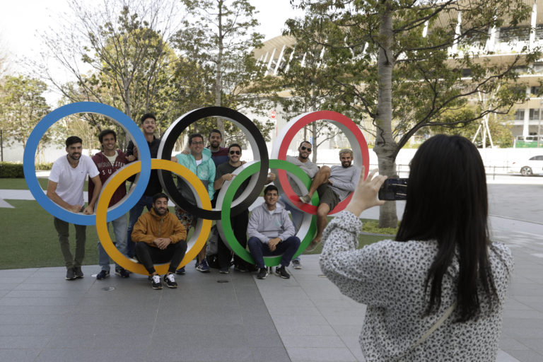 Một nhóm sinh viên đến từ Uruguay chụp ảnh lưu niệm trên các Nhẫn Olympic đặt bên ngoài Sân vận động Olympic ở Tokyo, Thứ Bảy, ngày 21 tháng 3 năm 2020. (Ảnh AP / Gregorio Borgia)
