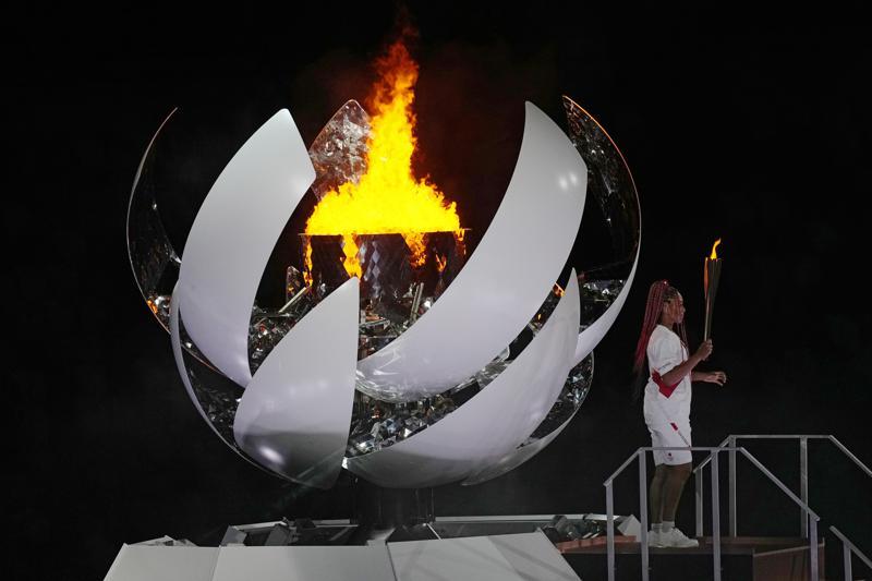 Naomi Osaka đứng bên ngọn lửa Olympic sau khi thắp sáng nó trong lễ khai mạc ở Sân vận động Olympic tại Thế vận hội mùa hè 2020, thứ Sáu, ngày 23 tháng 7 năm 2021, ở Tokyo, Nhật Bản. (Ảnh AP / David J. Phillip)