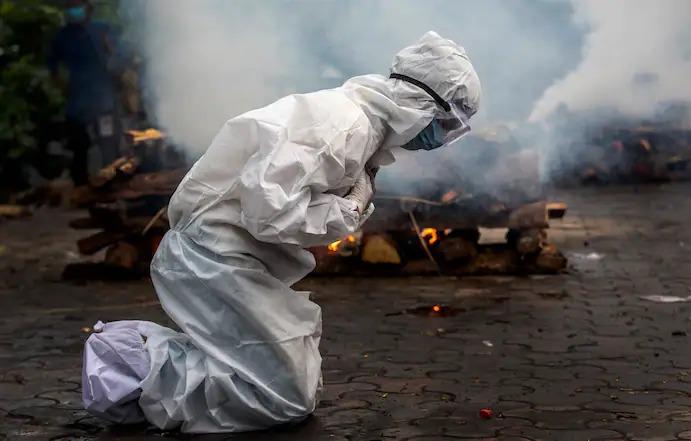 Một phụ nữ ở Gauhati, Ấn Độ, vỡ òa khi cầu nguyện trước lễ hỏa táng một người thân đã chết vì covid-19. (Anupam Nath / AP)